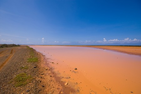salina: flat hato plateau curacao with a almost dryout salina lake and  red brown earth visable