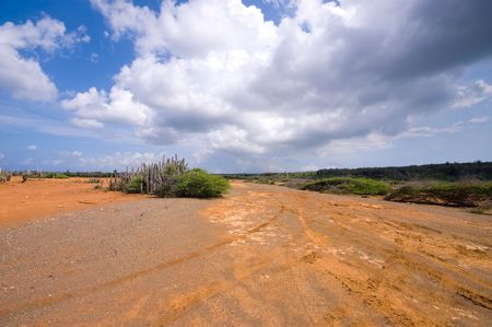 flat hato plateau curacao with a dark cloudy sky and  red brown earth visable