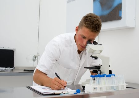 young scientist or student looking through a microscope and writing down data Stock Photo