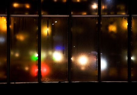 colorful lights showing trough some very dirty old glas window in iron frame