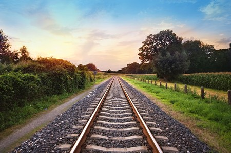 sun track: railway tracks in a rural scene with nice pastel sunset Stock Photo