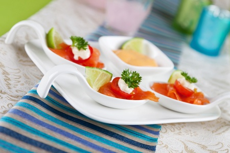 amuse: salmon served on a bouche spoon on a plate Stock Photo