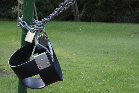 padlocked: A damaged swing is padlocked to a post so children can not play on it Stock Photo