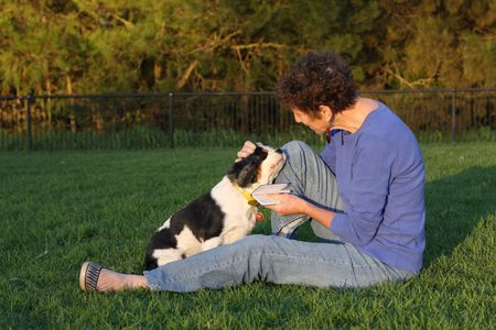 Mature woman and spaniel sitting in park photo