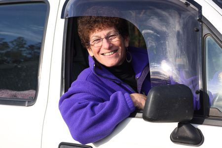 Senior woman smiling sitting in her car photo