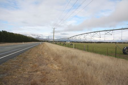 converge: Road powerlines fence and farm equipment converge to the horizon in rural New Zealand Stock Photo