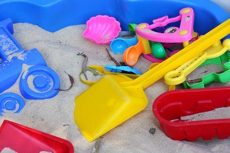 Colorful toys lie piled together in sandpit photo