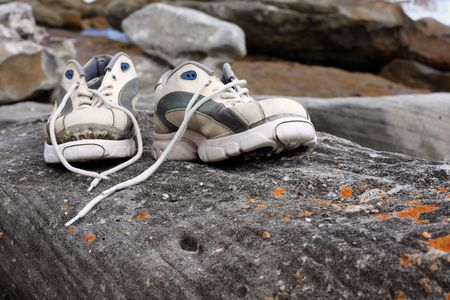 Pair of old worn sports shoes sit on rock photo