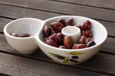 Bowl of tasty kalamata olives on wooden table photo