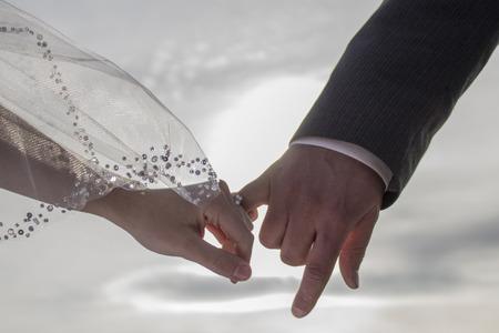 Bride and groom linking pinkies