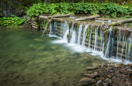 man made: creek and man made waterfall in the forest Stock Photo