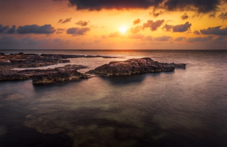 sunset over the sea and rocky coast photo