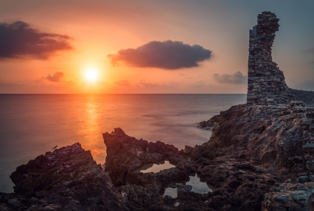 sunset over the sea and rocky coast with ancient ruins photo