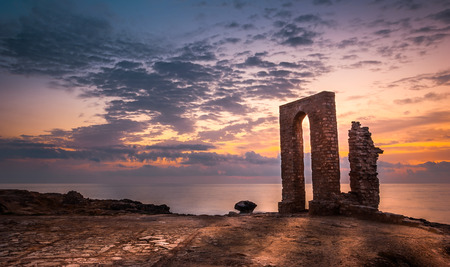 Sunset over the Sea and Rocky Coast with Ancient Ruins and Gate to Africa in Mahdia, Tunisia photo