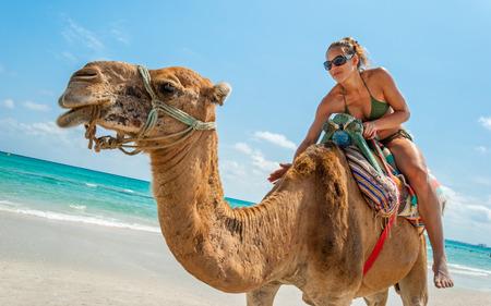 Mooie jonge vrouw zit op een kameel op het strand tijdens een tropische dag