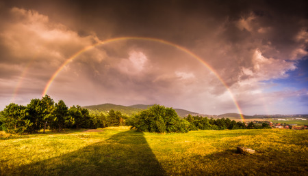 Double Rainbow over Landscape at Sunset with City of Nitra in Background photo