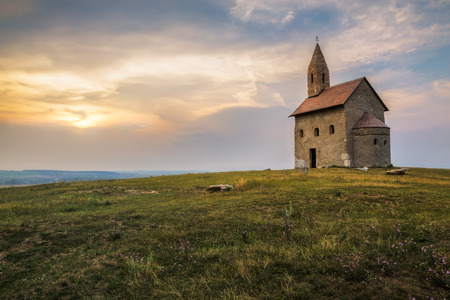 blue church: Old Roman Catholic Church of St. Michael the Archangel on the Hill at Sunset in Drazovce, Slovakia Stock Photo