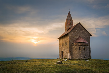 roman catholic: Old Roman Catholic Church of St. Michael the Archangel on the Hill at Sunset in Drazovce, Slovakia Stock Photo
