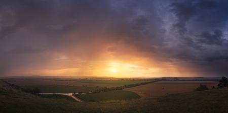 Colorful Sunset and Dramatic Sky over Illuminated Landscape photo