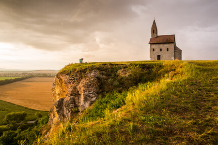 evening church: Man Taking Picture of Old Roman Catholic Church of St. Michael the Archangel on the Hill in Drazovce, Slovakia