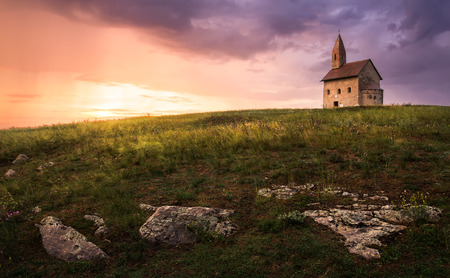 Old Roman Catholic Church of St. Michael the Archangel on the Hill at Sunset in Drazovce, Slovakia photo