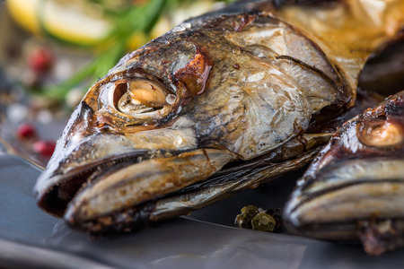 flavored: Baked Whole Mackerel Fish with Spice, Lemon and Rosemary on a Plate on Wooden Table
