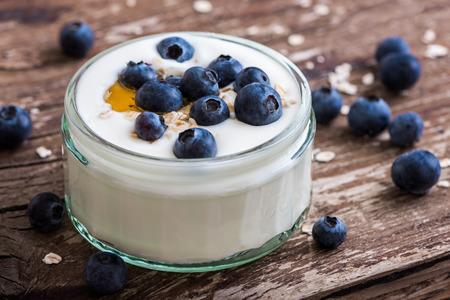 yaourt: Portion de yogourt avec entiers bleuets frais et Gruau Old Table en bois rustique. Détail Gros plan.