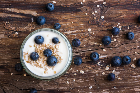 Serving of Yogurt with Whole Fresh Blueberries and Oatmeal on Old Rustic Wooden Table