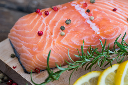 rosmarin: Raw Salmon Fish Fillet with Lemon, Spices and Fresh Herbs on Cutting Board
