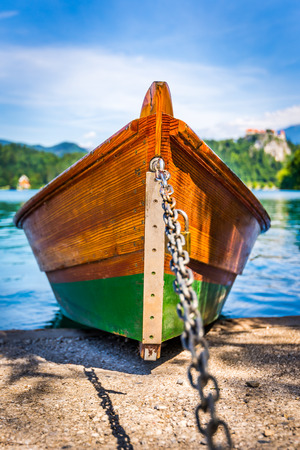 river boat: Detail of Anchored Wooden Tourist Boat on Shore of Bled Lake, Slovenia with Bled Castle in Background