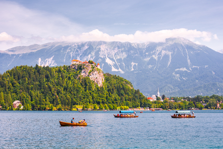 bled: BLED, SLOVENIA - AUGUST 1, 2015 - Bled Castle on a Precipice Overlooking Bled Lake with Tourists and Boats on August 1, 2015 in Bled, Slovenia