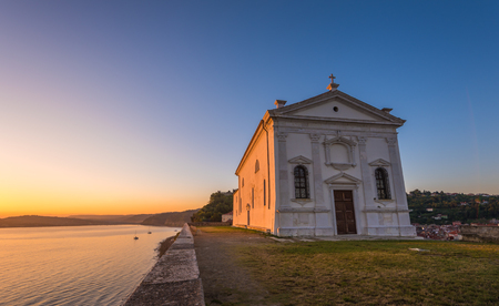 place to shine: St. Georges Church in Piran, Slovenia at Sunrise with Clear Blue Sky Stock Photo