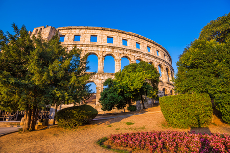 Ancient Roman Amphitheater in Pula, Croatia, Famous Travel Destination, in Sunny Summer Evening with Trees and Flowers in Foreground