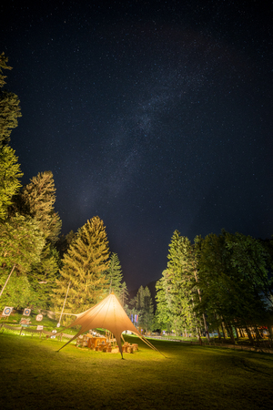 Camping Shelter Glows Surrounded by Trees Under a Night Sky Full of Stars Stock fotó