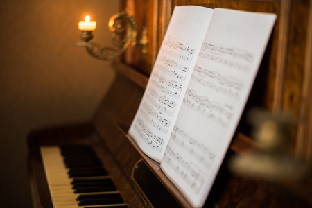 music book: Opened Music Book on Beautiful Old Piano with Burning Candle Stock Photo