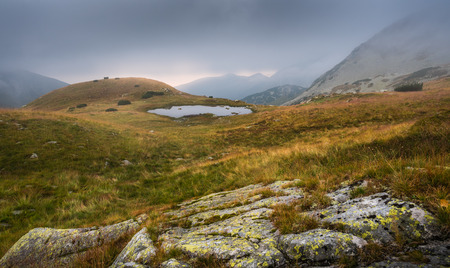 tarn: Foggy Mountain Landscape with a Tarn and a Rock in Foreground at Sunset