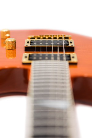 with orange and white body: Detail of Orange Electric Guitar Body with Defocused Fretboard Isolated on White Background