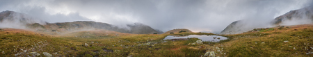 tarn: Wide Panoramic View of Small Tarn with Fog in West Tatra Mountains at Sunset Stock Photo