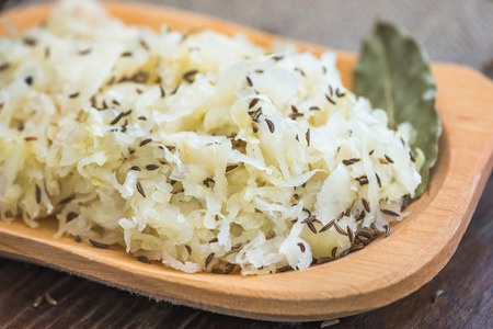 Closeup of Sour Cabbage with Cumin and Bay Leaf on Wooden Plate