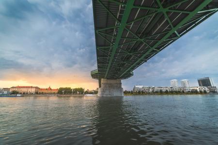 By the River under the Bridge. Skyline of Bratislava, Slovakia at Sunset in Background. Reklamní fotografie