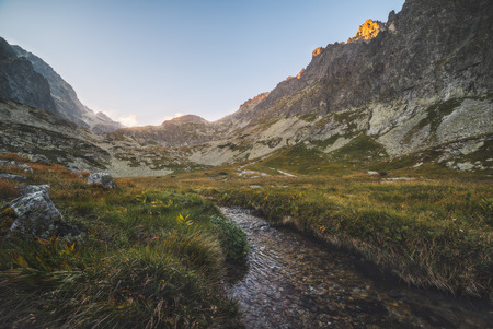 Creek in the Valley under the Mountain Peaks at Sunset. Velicka Valley, High Tatra, Slovakia.