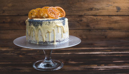 Poppy Seed Cake with White Chocolate and Caramelized Orange on Rustic Wooden Background