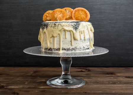 Poppy Seed Cake with White Chocolate and Caramelized Orange on Rustic Wood