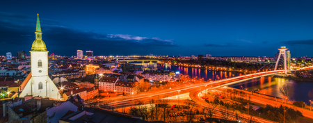 Cityscape of Bratislava, Slovakia with St. Martin's Cathedral and Danube River with New Bridge at Night