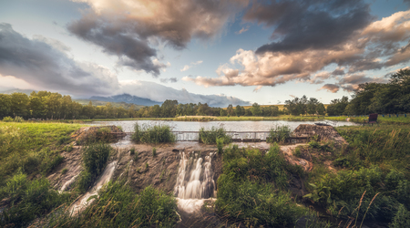 Strba Pond lit by Golden Light at Sunset with High Tatras Mountains in Background, Slovakia.