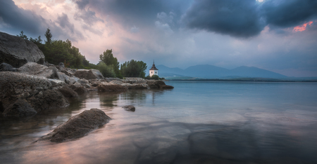 Virgin Mary Church by Liptovska Mara Lake with Western Tatras Mountains in Background at Sunset in Slovakia Banco de Imagens