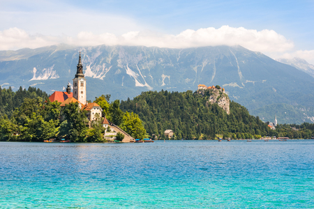 Little Island with Catholic Church and Bled Castle on Bled Lake, Slovenia with Mountains in Background 免版税图像