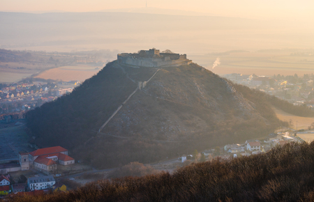 Ruin of the Castle on the Hill at Sunrise. Schlossberg Castle in Hainburg an der Donau, Austria at Sunrise as Seen from Hundsheimer Hill. 免版税图像