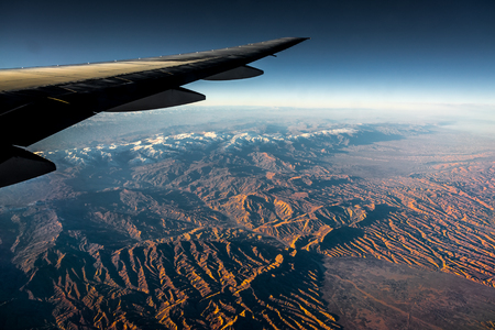Aerial View from an Airplane. Flying above Beautiful Land at Sunrise. Фото со стока