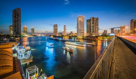 Skyscrapers and Light Trails of Traffic on the Chao Phraya River in Bangkok, Thailand as Seen from Taksin Bridge at Twilight Stockfoto